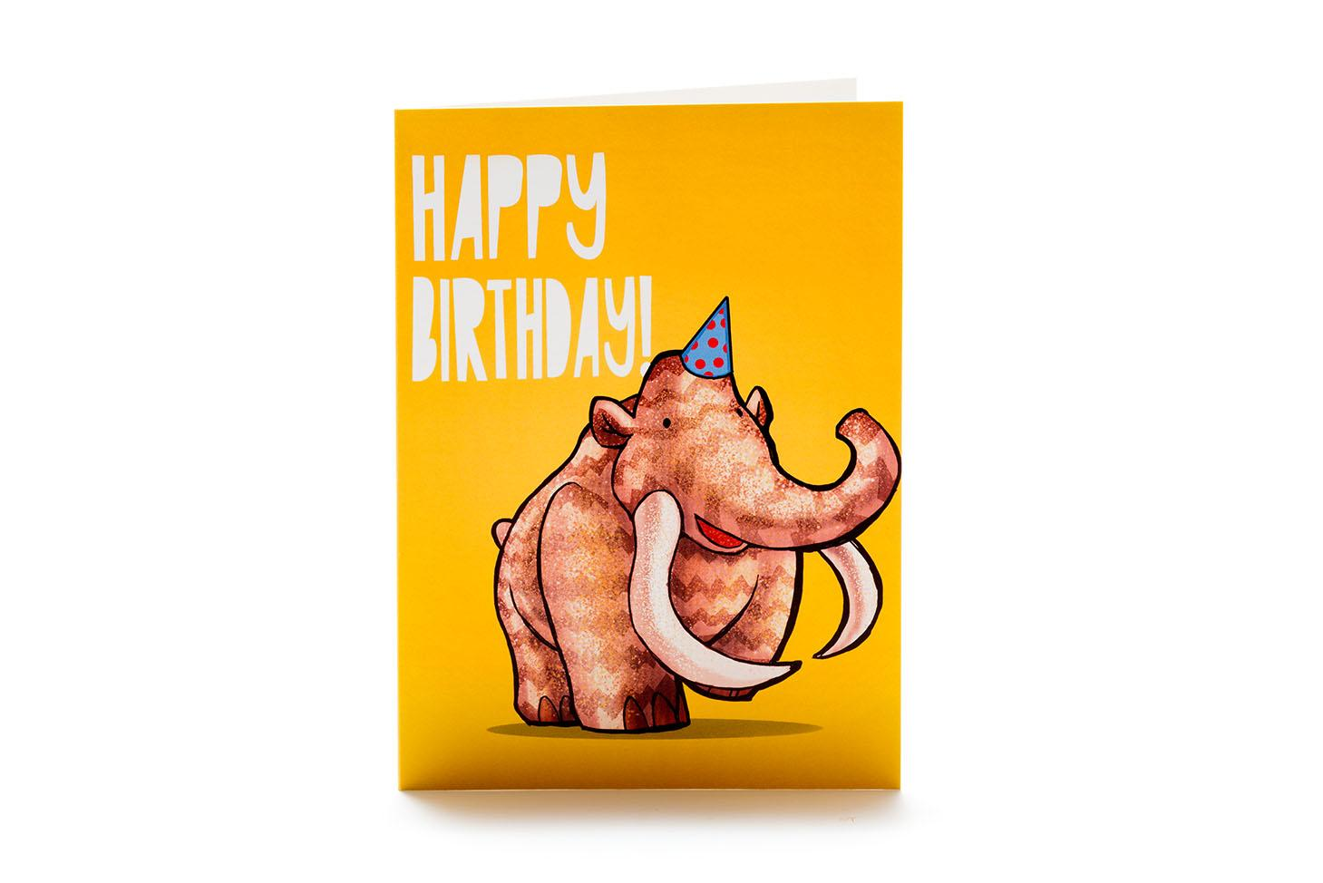 Orange greetings card featuring mammoth cartoon in party hat with happy birthday in white writing