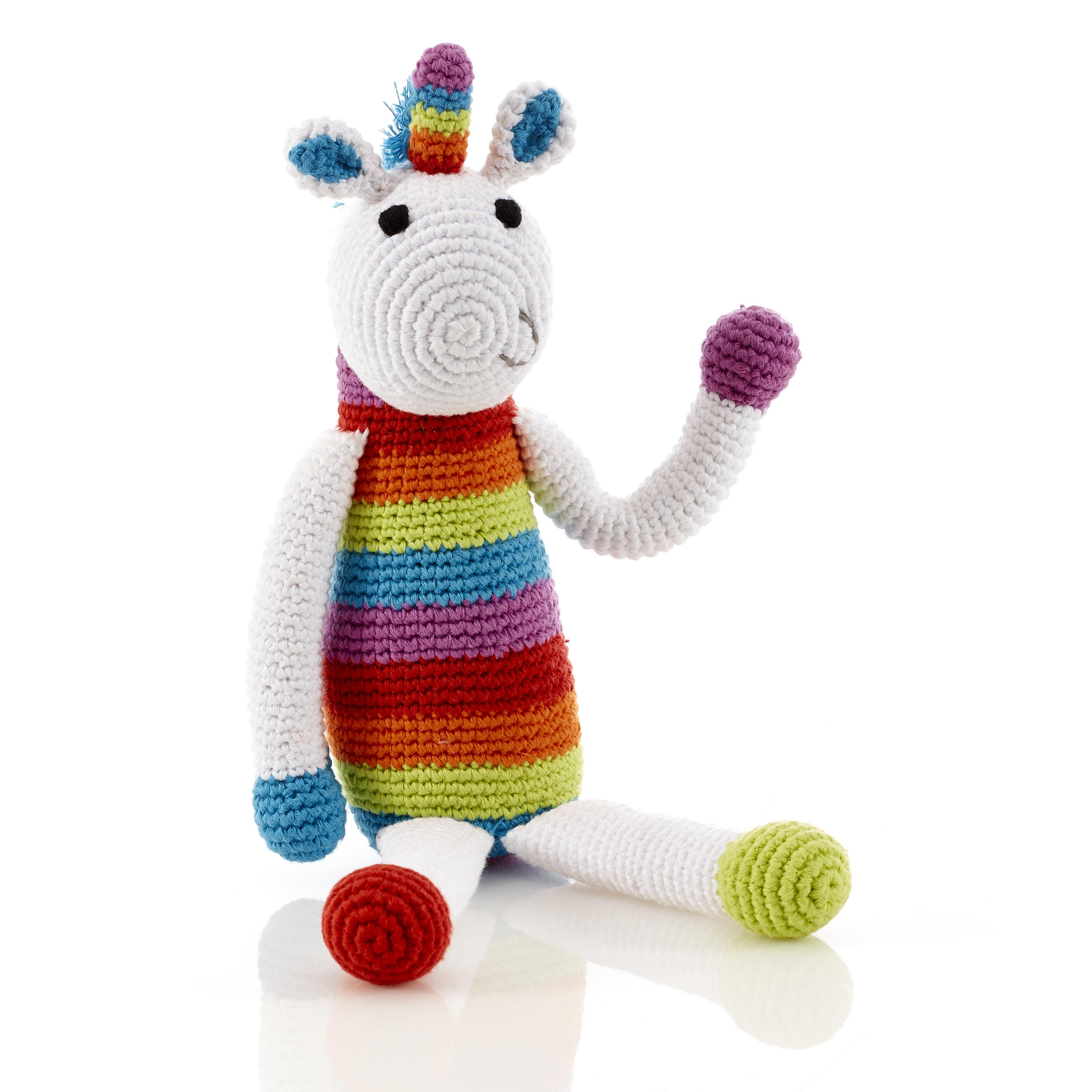 Unicorn baby rattle crochet from cotton with rainbow stripe body, white arms and colourful horn.
