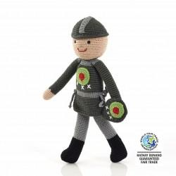 fair trade crochet cotton medieval knight doll in grey clothing with green and red shield details and grey hat