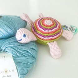 Crochet Cotton Turtle Baby Rattle with blue, green and red stripes and smiley face