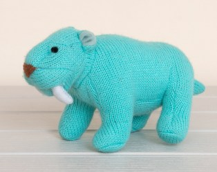 Turquoise blue knitted sabre tooth tiger soft toy on white wood surface