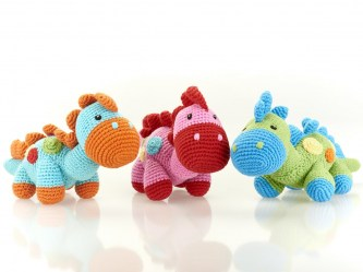 fair trade crochet cotton pink dinosaur baby rattle with red spine and pastel coloured dots on its body