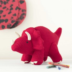Greetings card with picture of red triceratops dinosaur knitted soft toy with crayons and painting behind