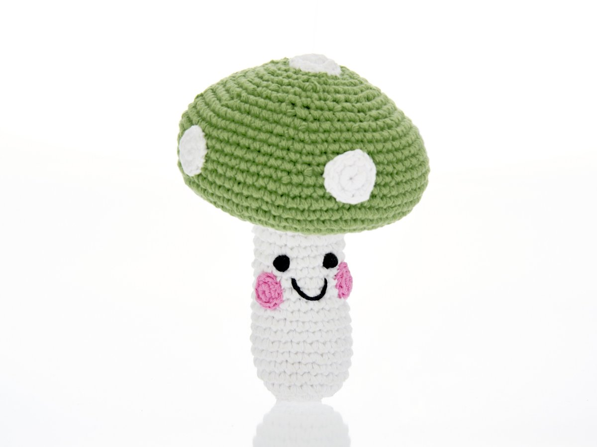Crochet toadstool baby toy with white stalk and smiley face and green cap with white dots