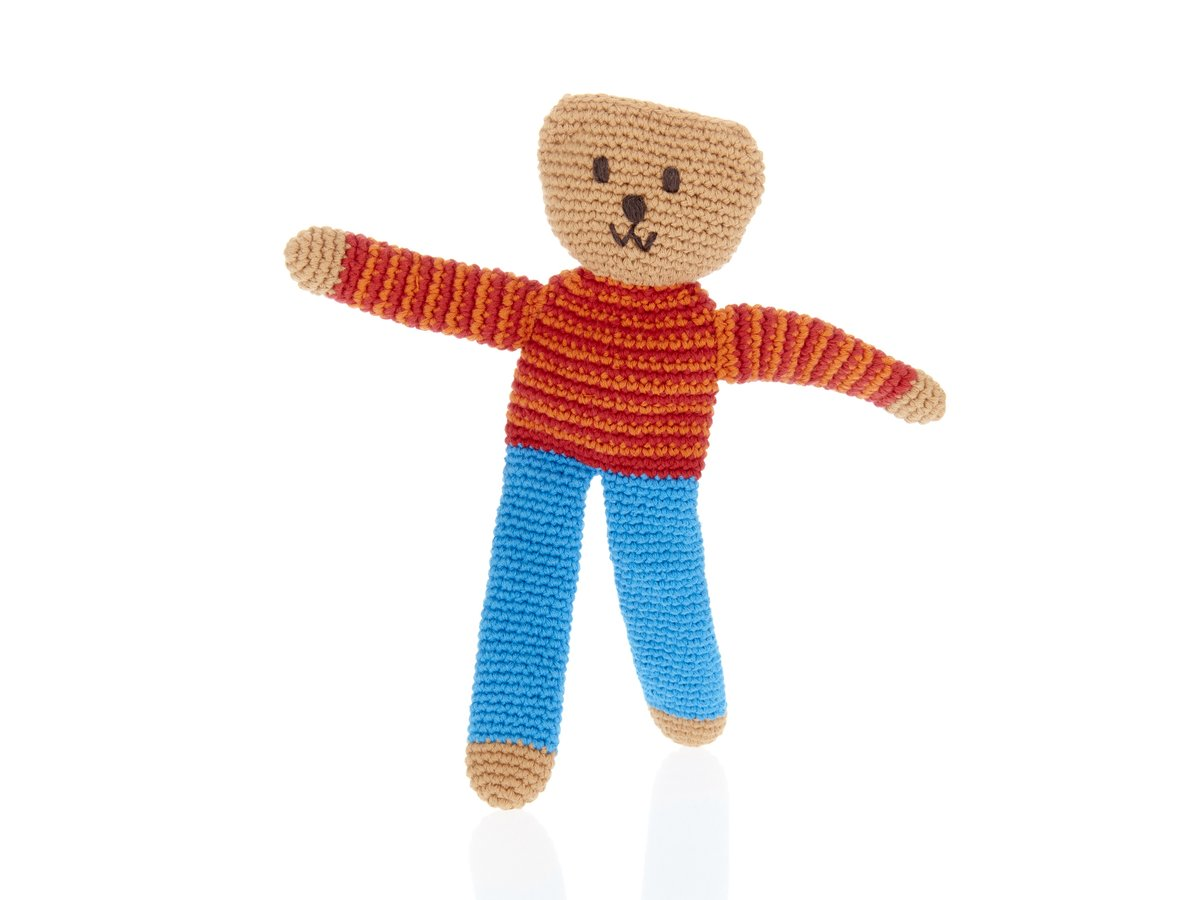 Crochet first teddy bear soft toy with long legs in blue trousers and red and orange stripe jumper.