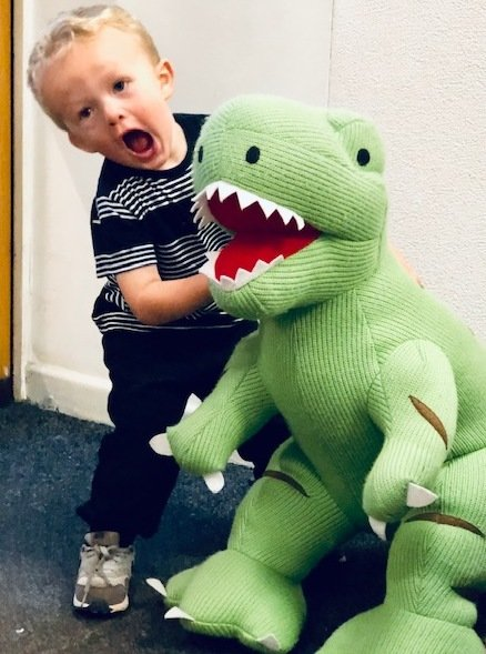 Giant knitted green T rex dinosaur toy and young boy
