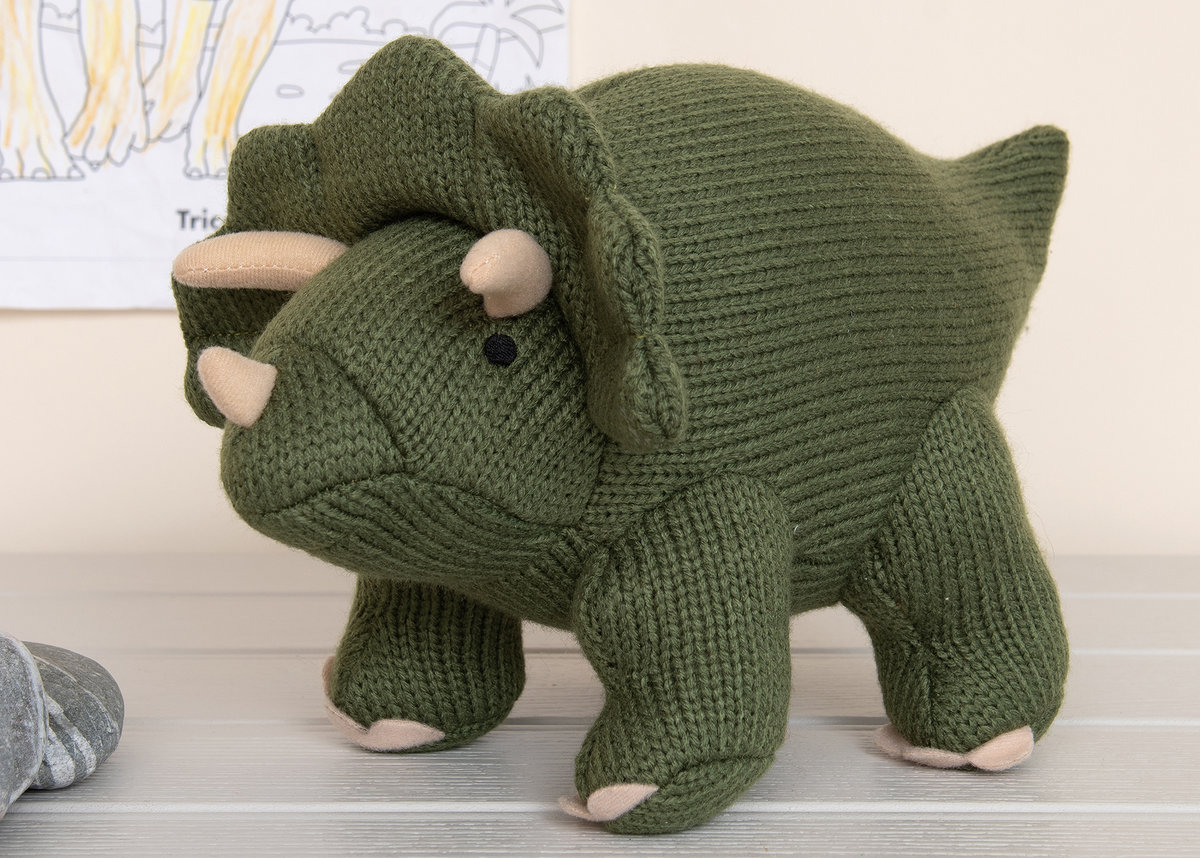 Knitted moss green triceratops dinosaur soft toy on white floorboards with drawing on the wall behind